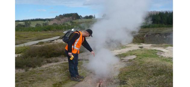 Worker next to steam vent in ground